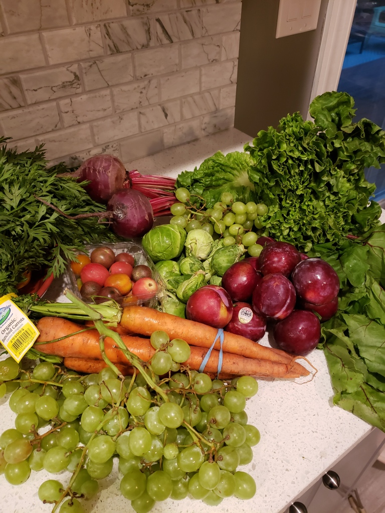Grapes, carrots, heirloom cherry tomatoes, brussel sprouts, pluots, beets and green leaf lettuce.