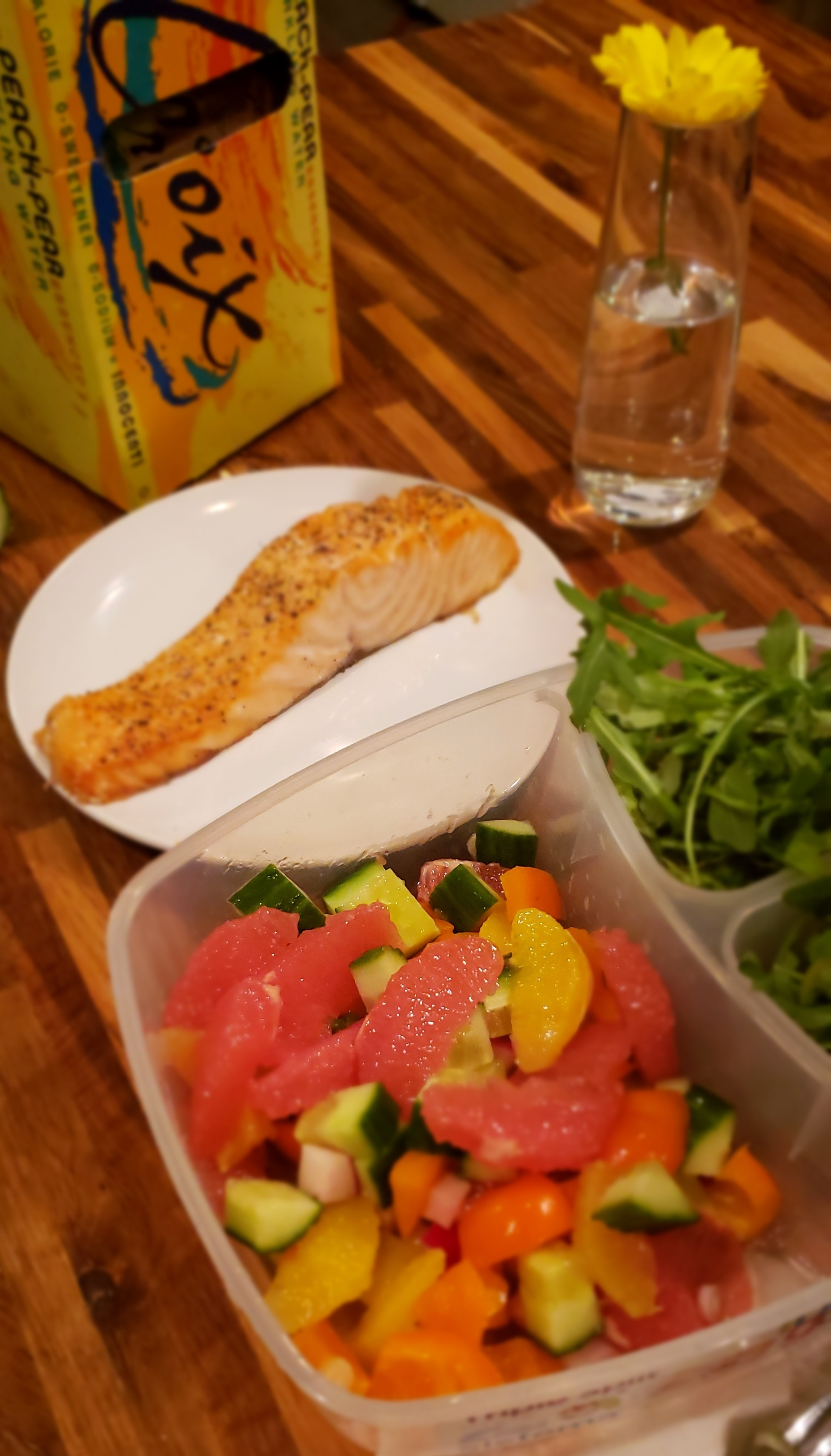 Dressed, chopped veggies are stored separate from the arugula in a to-go container. Salmon on the side.