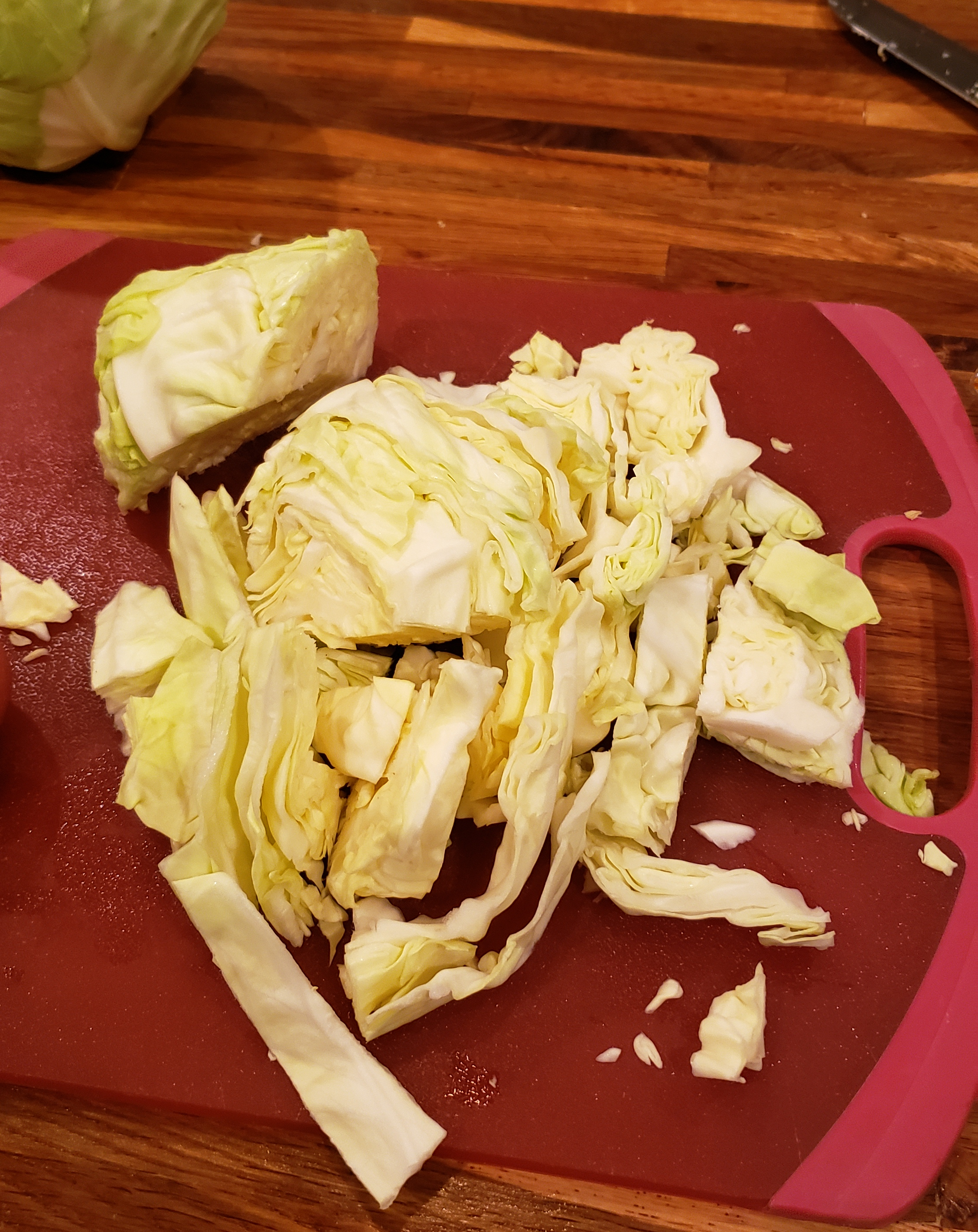 Thickly sliced cabbage on a cutting board.