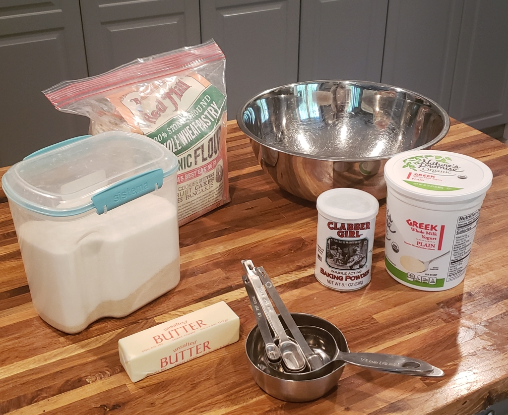 Butter, sugar, flour, big silver bowl, baking powder, Greek yogurt and measuring spoons and cups.