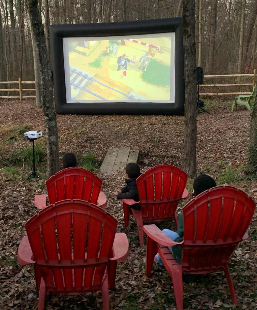 Kids watch a movie on the big screen in our backyard. Equipment furnished by Family Backyard Rentals.