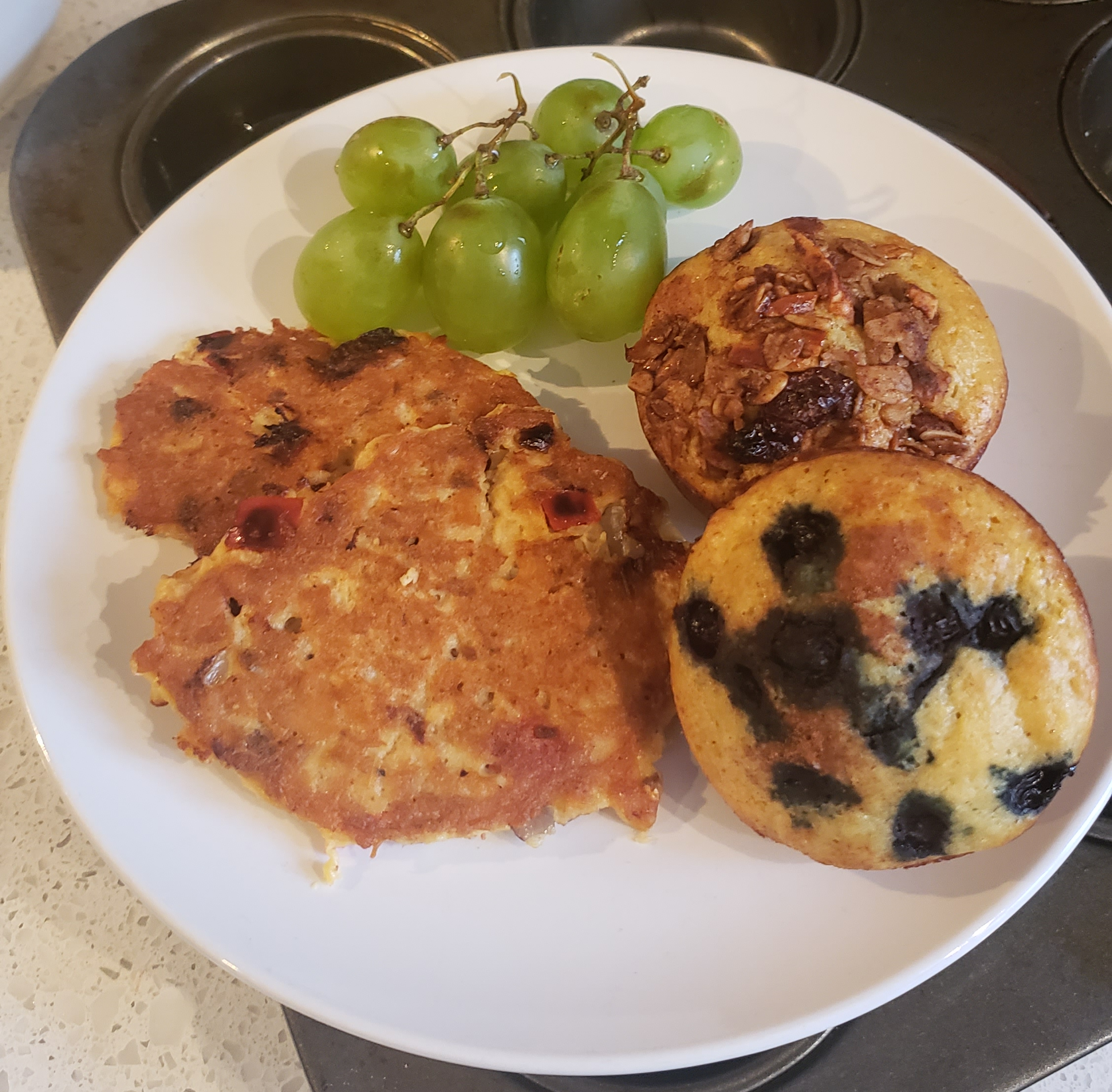 A plate with pancake muffins, salmon cakes and grapes.