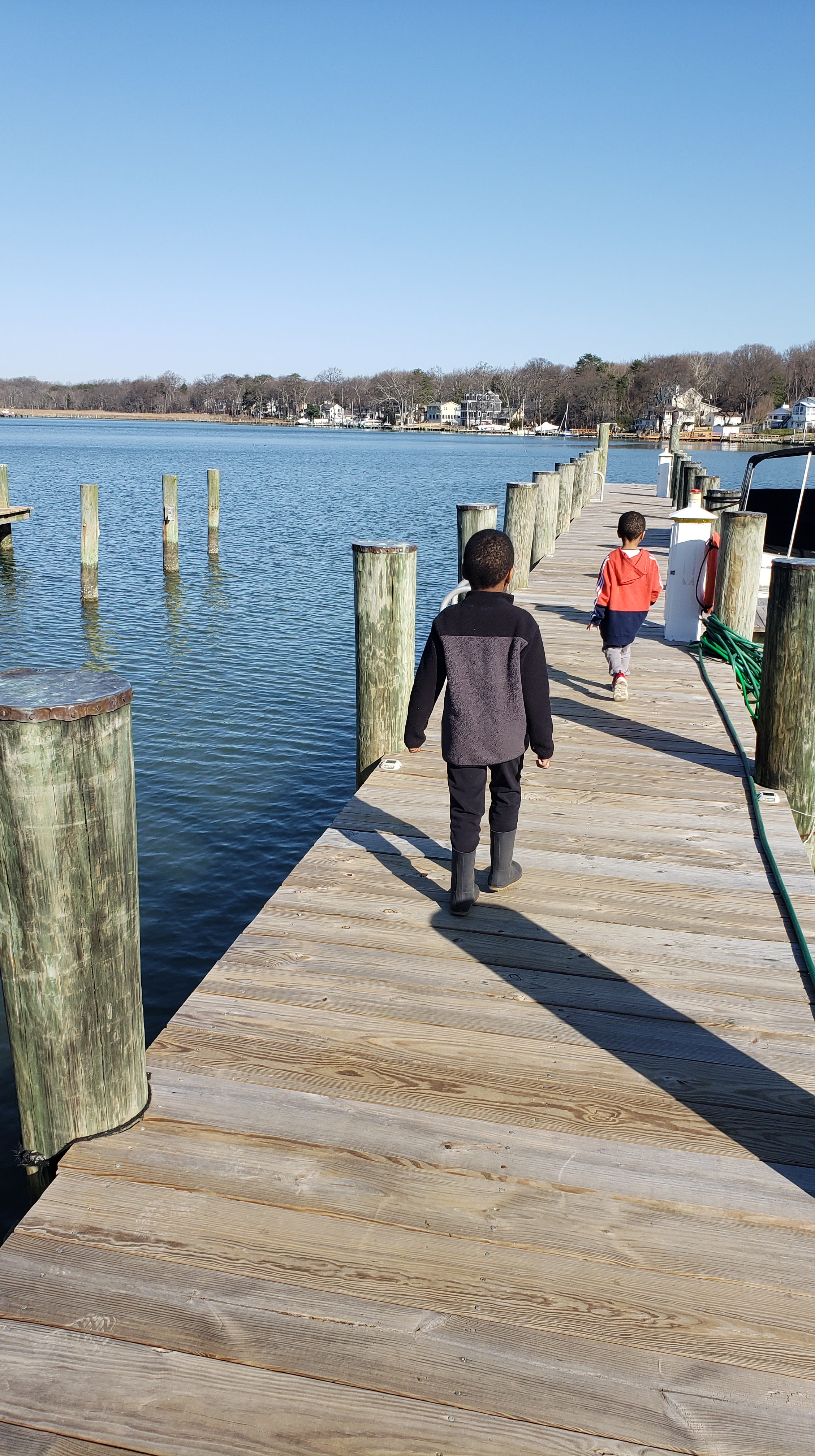 Two kids walking down a pier.